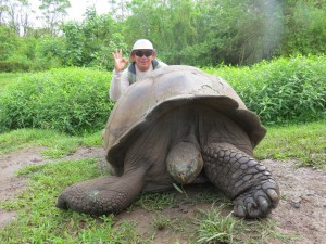 Harry with an endemic Giant Galapagos tortoise in the wild in Santa Cruz Highlands